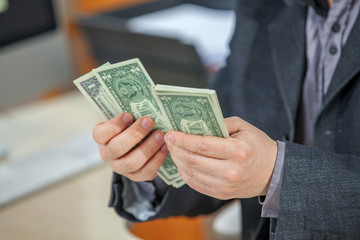 A businessman is very successful in his business and now, he is counting the money in his hands.