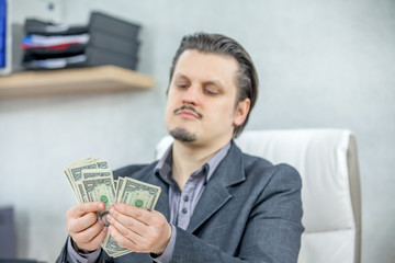 A young businessman is counting the money in his hands. He is sitting in his office.