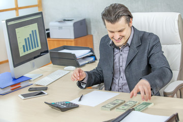 A businessman looks very happy when he sees all the money on the table.