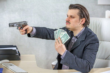 A businessman is sitting at the table in his office. In one hand, he is having a gun and in the other lots of money.