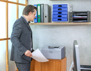 A businessman is waiting for something to be printed out of the printer.