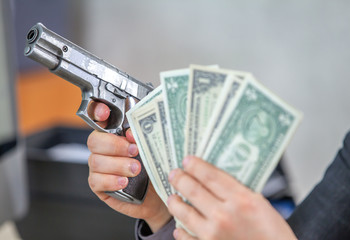 Having money in one hand and a gun in the other. He is pointing a gun at someone.