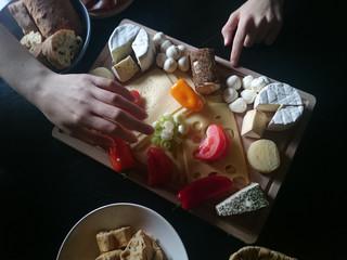 Käseplatte mit Händen die zum Käse greifen