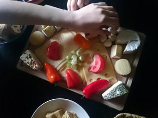 Käseplatte mit Händen die nach Käse greifen