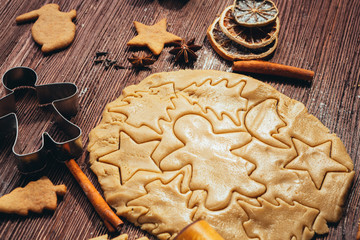 Gingerbread dough with molds for baking cinnamon on dark wooden table