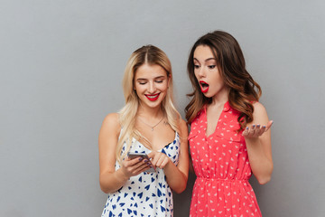 Shocked young ladies looking at phone.