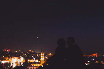 Couple on Valide Han roof. Illuminated lights of night Istanbul view