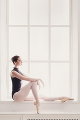 Classical Ballet dancer portrait at window background