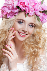 Beauty woman on a white background . Bright wavy hair and a wreath of pink peonies
