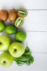 Ingredients for smoothie. Green fruits on white wooden background. Apple, lime, spinach, kiwi. Detox. Healthy food. Top view.