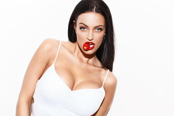 Sexy woman with red lips and big tits eating strawberry