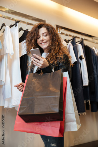 725fcd8330 Cheerful curly young lady in clothing shop with shopping bags ...