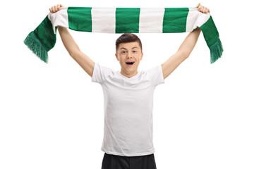 Overjoyed teenage football fan holding a scarf
