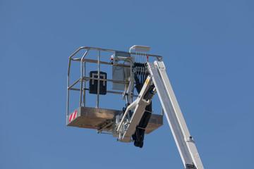 Arbeitskorb - Personenkorb von einem Steiger - Hubwagen in der Luft vor blauem Himmel