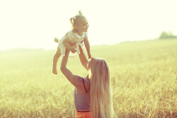 young mother and daughter kissing in the summer in wheat field