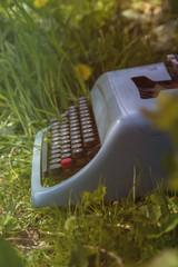 blue typewriter on the grass
