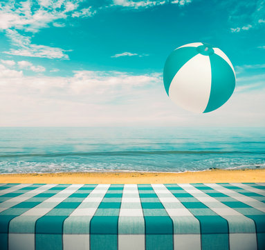 Picnic table at the beach with flying beachball