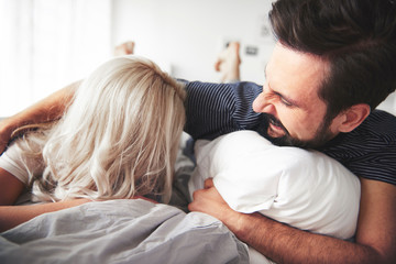 Couple lying on bed, man tickling woman