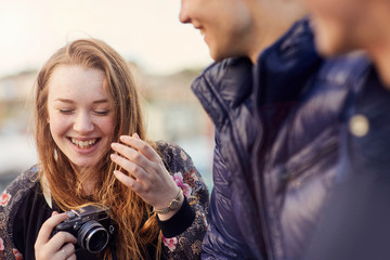 Three friends outdoors, young woman holding camera, laughing, Bristol, UK