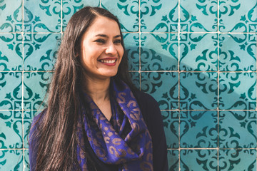 Portrait of woman in front of colourful tiled wall, Lisbon, Portugal