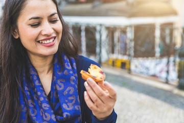 Woman holding pastel de nata, Lisbon, Portugal