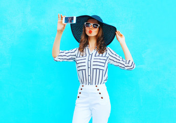 Fashion young woman is taking a picture on a smartphone wearing a straw summer hat, white pants over colorful blue background