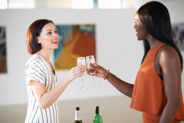 Two women raising a white wine toast at art gallery opening