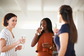 Three women chatting and drinking white wine at art gallery opening
