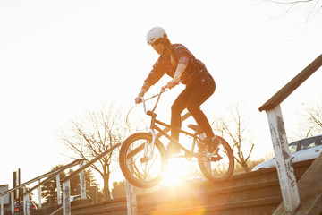 Female BMX rider riding down sunlit stairway