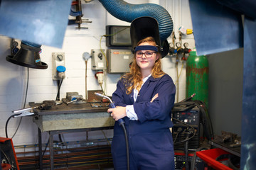 Portrait of female higher education student holding welding torch in workshop at college