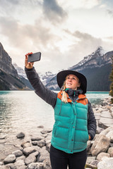 Woman standing at edge of lake, taking selfie with smartphone, Lake Louise, Alberta, Canada