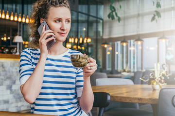 Young cheerful businesswoman in striped T-shirt is sitting at table in cafe, drinking coffee and talking on cell phone.