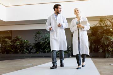 Two doctors walking, female doctor holding digital tablet