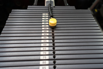 Black metallic or iron heavy plates stacked for sport, exercise, weight machine with kilogram and pound numbers in fitness gym
