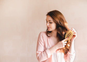 Beautiful young woman combing brushing her long smooth hair with a wooden comb. Haircare concept.