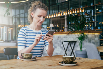 Young business woman sitting at table in cafe and using smartphone.