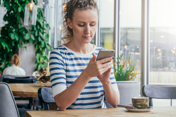 Woman in striped T-shirt is sitting at table in cafe near window and is using smartphone. On table is cup of coffee.