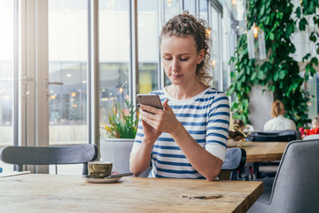 Young business woman in striped T-shirt is sitting at table in cafe near window and is using smartphone.
