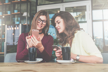 Two young cheerful women sit at table in cafe and use smartphone.