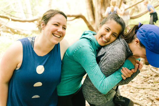Three adult sisters hugging and laughing in forest, Maine, USA