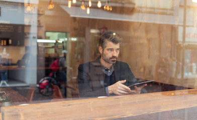 man working on a digital project in a cafe