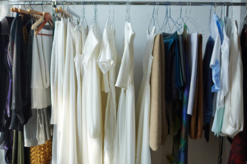 Row of dresses, shirts and fabric on hangers in tailoring shop