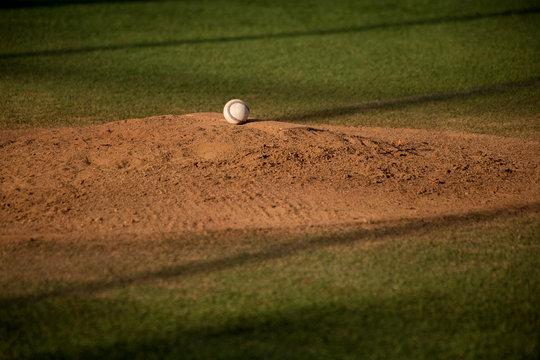 Baseball ball on sand mound on baseball field