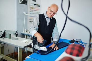 Senior man ironing sleeve of jacket in his tailoring-shop