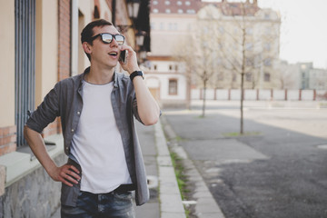 Happy young hipster man walking on the street and talking on phone