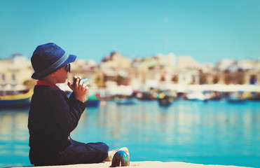 little boy taking photos on the quay of Malta, Europe