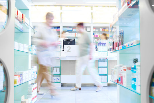 Defocused picture of customers shopping in pharmacy .