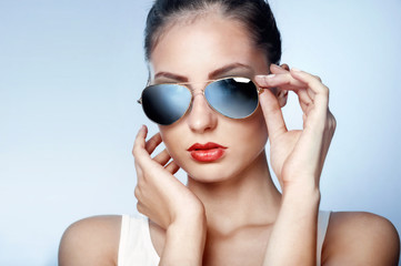 Stylish young woman in blue mirrored sunglasses
