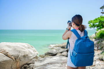 Backpacking women is taking the photo with digital camera on the seashore