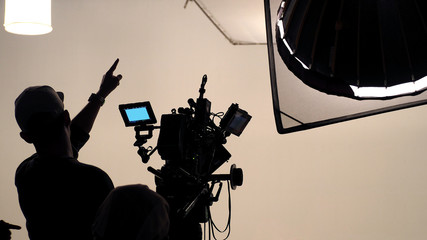 Behind the scenes of silhouette working people or video production film crew are making movie or shooting TV commercial with high quality professional equipment in studio.